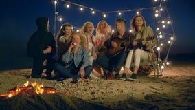Развлечения пляжа молодости, счастливые люди играя гитару и поя сидеть костром в песке на обваловке видеоматериал