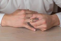 Развод, разъединение: человек извлекая свадьбу или обручальное кольцо стоковая фотография