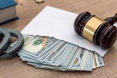 развращение доллары в конверте, наручники, молоток стоковая фотография