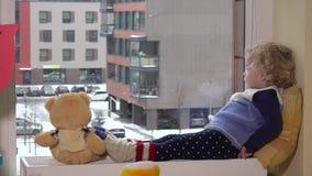 Разговаривать ребенка девушки малыша при плюшевый медвежонок возбужденный для того чтобы увидеть снег снаружи акции видеоматериалы