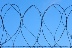 Разделительная стена колючего провода бритвы военная против голубого неба стоковые фото
