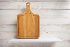 Разделочная доска на деревянной полке стоковое фото rf