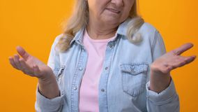 Раздражанная бабушка показывая жестами руки на желтой предпосылке, отрицательном отклике сток-видео