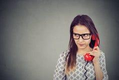 Раздражанная женщина имея дилемму во время телефонного звонка стоковые фотографии rf