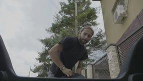 Раздражанные тысячелетние одетые случайные человека кладущ чемодан в багажник автомобиля подготавливая выйти для работы - акции видеоматериалы