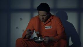 Раздражанный пленник смотря с отвращением на неаппетитной еде, плохими условиями видеоматериал