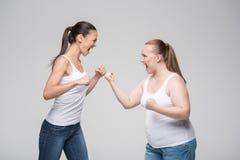 Раздражанный толстый и худенький бой девушек Стоковая Фотография