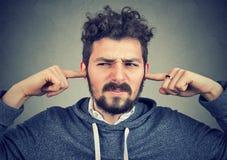 Раздражанный человек затыкая уши надоел сильным шумом стоковая фотография rf