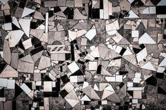 Раздробите сломленные плитки на участки B&W на предпосылке текстуры стены Стоковые Фото