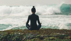 Раздумье женщины йоги на крае скалы взморья стоковое фото rf