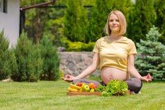 Раздумье и релаксация беременной женщины практикуя в природе Стоковые Изображения