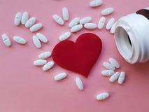 Разлейте фармацию по бутылкам предпосылки сердца белых медицинских пилюлек розовую Стоковые Изображения RF