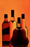 разливает виски по бутылкам водочки конгяка Стоковые Фотографии RF