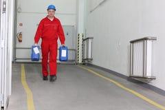 разливает заводской рабочий по бутылкам нося химикатов Стоковое Фото