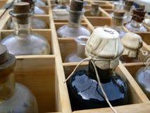 разливает микстуру по бутылкам старую Стоковое фото RF