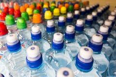 разливает пластичную воду по бутылкам Бутылки с водой, красочные крышки Стоковые Изображения RF