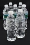разливает пластичную воду по бутылкам стоковые изображения