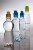 разливает пластичную воду по бутылкам Стоковое фото RF