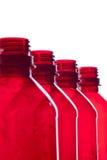 разливает пластичный красный цвет по бутылкам Стоковые Изображения