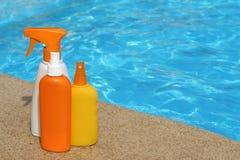 разливает солнцезащитный крем по бутылкам suncare продуктов стоковые изображения rf