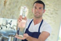 Разливая по бутылкам работник показывая лимонад бутылки Стоковое Фото