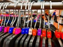 Различная определенная размер вешалка с красочным размером платья маркирует XL L футболки m XS показанные в магазине для продажи стоковые изображения rf