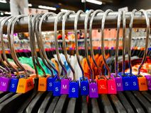 Различная определенная размер вешалка с красочным размером платья маркирует XL L футболки m XS показанные в магазине для продажи стоковое изображение rf