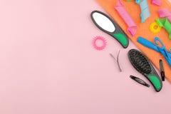 Различные аксессуары, curlers, гребни, barrettes и эластичные резиновые ленты волос на яркой розовой предпосылке Взгляд сверху с  стоковые фотографии rf