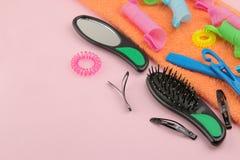 Различные аксессуары, curlers, гребни, barrettes и эластичные резиновые ленты волос на яркой розовой предпосылке Взгляд сверху с  стоковая фотография
