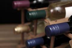 Различные бутылки красного и белого вина в деревянном вине кладут на полку Стоковое Изображение