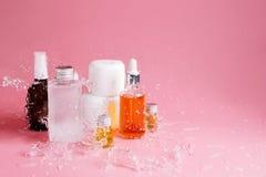 Различные бутылки, опарникы и контейнеры с косметиками на пинке с брызгать воды Стоковые Фото