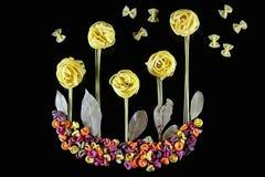 Различные виды покрашенных сырцовых итальянских макаронных изделий на черной предпосылке, взгляд сверху, в форме полей цветка и б Стоковое фото RF