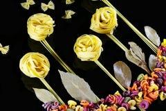 Различные виды покрашенных сырцовых итальянских макаронных изделий на черной предпосылке, взгляд сверху, в форме полей цветка и б Стоковое Изображение