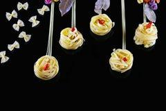 Различные виды покрашенных сырцовых итальянских макаронных изделий на черной предпосылке, взгляд сверху, в форме полей цветка и б Стоковые Изображения RF