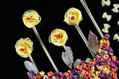 Различные виды покрашенных сырцовых итальянских макаронных изделий на черной предпосылке, взгляд сверху, в форме полей цветка и б Стоковые Фотографии RF