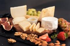 различные виды сыров, меда, смокв, гаек, виноградин, и плодоовощ на таблице Селективный фокус скопируйте космос стоковые фото