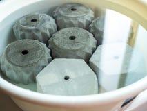 Различные геометрические конкретные плантаторы в белом пластиковом тазе с водой стоковые изображения rf