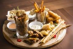 Различные закуски пива: кольца calamari, фраи, горячие крыла, хлеб Стоковое Фото