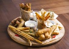 Различные закуски пива: кольца calamari, фраи, горячие крыла, хлеб Стоковое Изображение