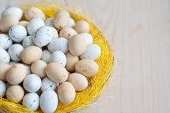 Различные изменения пасхальных яя в плетеной плите на светлой предпосылке Стоковая Фотография