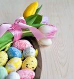 Различные изменения пасхальных яя в плетеной плите на светлой предпосылке Стоковые Фотографии RF