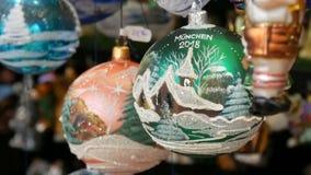 Различные красивые шарики и игрушки рождества для того чтобы украсить ель рождества на счетчике рынка Надпись на немецком сток-видео