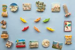 Различные магниты сувенира и корабли бумаги аранжировали на голубой предпосылке стоковое фото