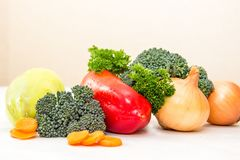 Различные овощи и свежие травы с waterdrops на белой таблице Оранжевые куски ростков моркови и брокколи Стоковые Изображения RF