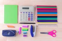 Различные пестротканые аксессуары канцелярских принадлежностей и школы на естественном деревянном столе стоковое фото rf