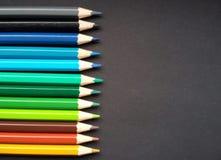 Различные покрашенные карандаши над черной предпосылкой стоковые изображения
