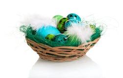 Различные покрашенные пасхальные яйца в корзине изолированной на белизне Стоковое Изображение