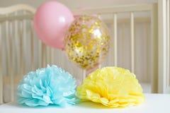 Различные праздничные бумажные оформление и воздушные шары перед кроватью младенца Интерьер спальни младенца Стоковое Изображение