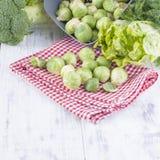 Различные свежие зеленые овощи, ростки Брюсселя и овощи На белой деревянной предпосылке место текста сочинительства Стоковая Фотография