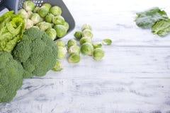 Различные свежие зеленые овощи, ростки Брюсселя и овощи На белой деревянной предпосылке место текста сочинительства Стоковые Фото